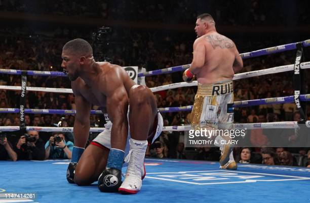 England's Anthony Joshua kneels after being knocked down by USA's Andy Ruiz in the 7th round to win by TKO during their 12round IBF WBA WBO IBO World...