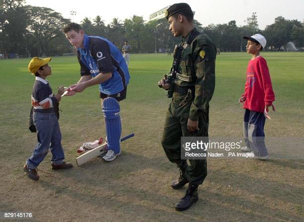 England's Ashley Giles signs an autograph watched by an armed Indian Army Commando after the match against a Bengal Cricket Association XI at the...