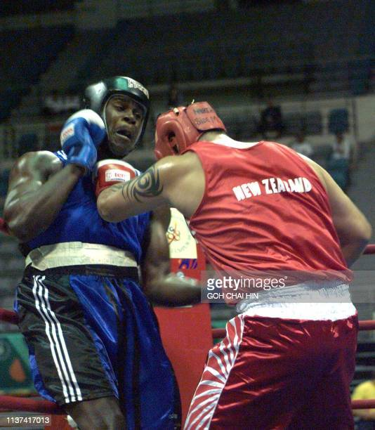 England's Audley Harrison lands a punch to the stomach of New Zealand's Paufaii Falamoe in the over 91kg category quarterfinal bout of the...