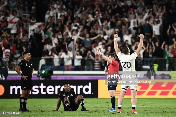 TOPSHOT England's back row Mark Wilson reacts beside New Zealand's flyhalf Richie Mo'unga and New Zealand's wing Sevu Reece after winning the Japan...