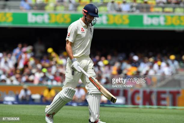 England's batsman Alastair Cook walks off the field following his dismissal off Australia's paceman Mitchell Starc on the first day of the first Test...