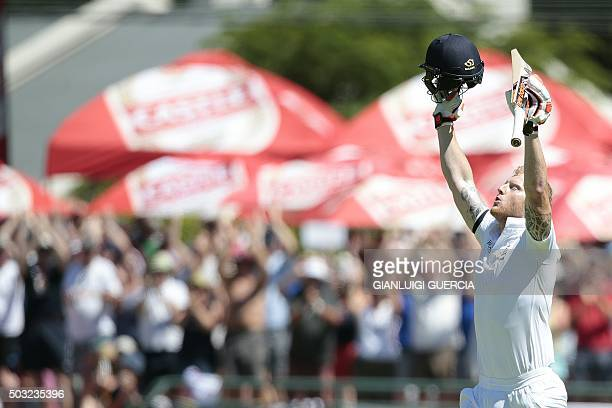 England's batsman Benjamin Stokes raises his bat and helmet as he celebrates scoring a century during the day two of the second Test match between...