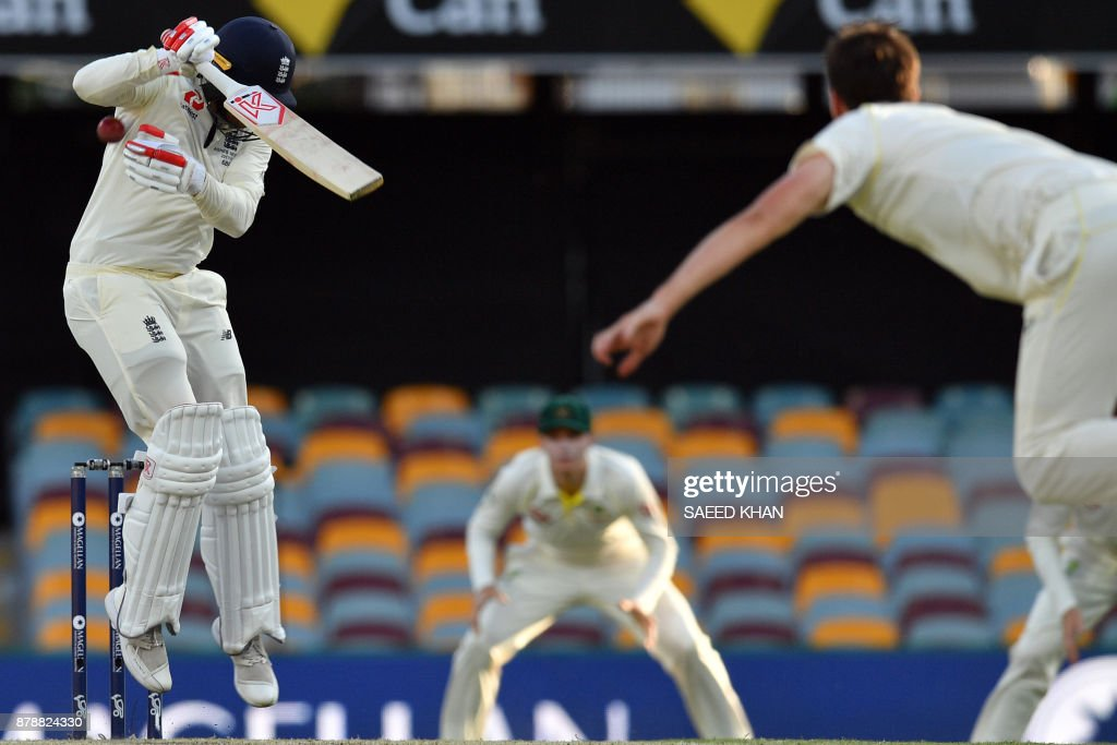 England's batsman Mark Stoneman (L) avoids a bouncer delivery by Australia's paceman Pat Cummins (R) on the third day of the first cricket Ashes Test between England and Australia in Brisbane on November 25, 2017. / AFP PHOTO / Saeed KHAN / -- IMAGE