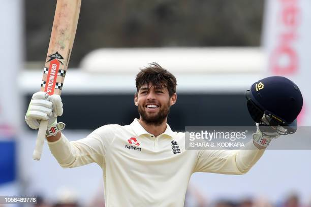 England's Ben Foakes raises his bat and helmet in celebration after scoring a century during the second day of the opening Test match between Sri...