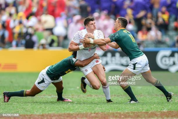 England's Ben Howard tries to break the tackle of South Africa's Muller du Plessis during the second day of the Hong Kong Sevens rugby tournament in...
