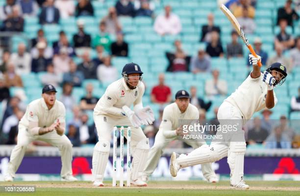England's Ben Stokes and England's Jonny Bairstow watch as India's Rishabh Pant plays a shot for six runs during play on the final day of the fifth...
