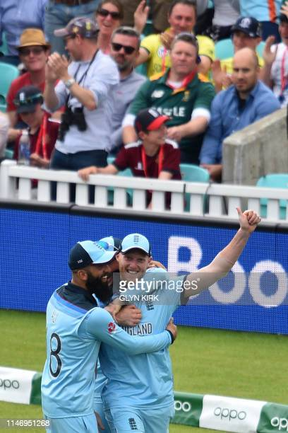 England's Ben Stokes celebrates with teammates after taking the catch to dismiss South Africa's Andile Phehlukwayo for 24 during the 2019 Cricket...