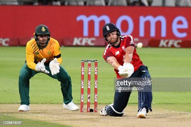 England's Ben Stokes hits a six as South Africa's captain Quinton de Kock looks on during the first T20 international cricket match between South...