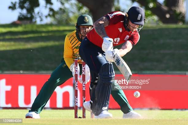 England's Ben Stokes plays a shot as South Africa's captain and wicketkeeper Quinton de Kock looks on during the second T20 international cricket...