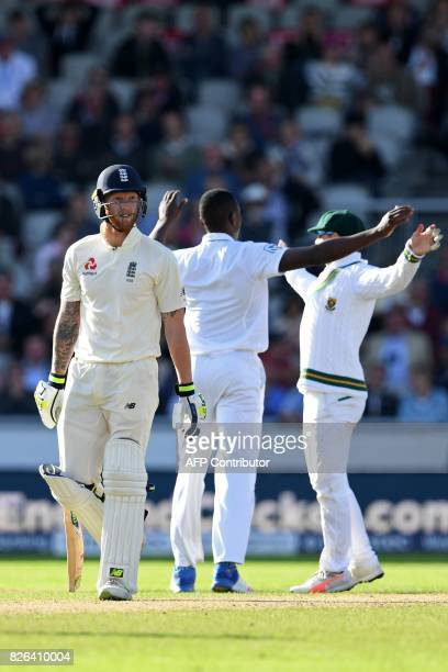 England's Ben Stokes walks back to the pavilion as South Africa's Kagiso Rabada celebrates bowling him for 58 during play on the day 1 of the fourth...
