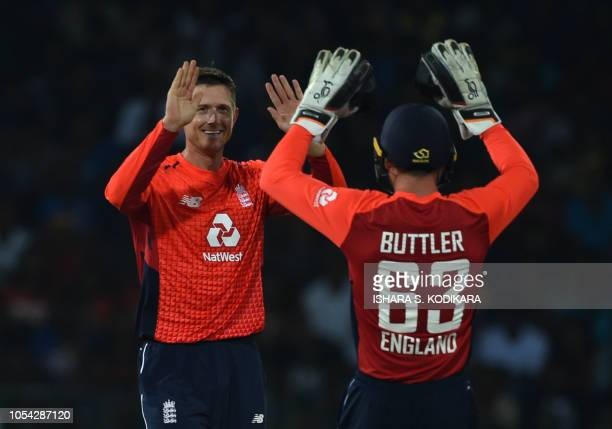England's bowler Joe Denly celebrates with England's wicketkeeper Jos Buttler after he dismissed Sri Lankan cricketer Niroshan Dickwella during the...