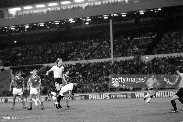 England's Bryan Robson directs a diving header towards goal only to be saved by East Germany goalkeeper Rene Muller England's Mark Wright looks on