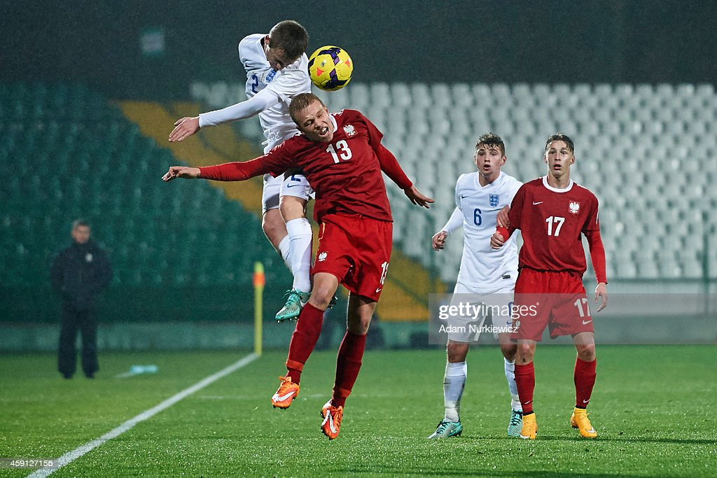 England's Callum Connolly (L) fights for the ball with Poland's Karol Zmijewski during the international friendly match Under-18 between Poland and England on November 17, 2014 on the MOSiR Stadium in Gdansk, Poland.