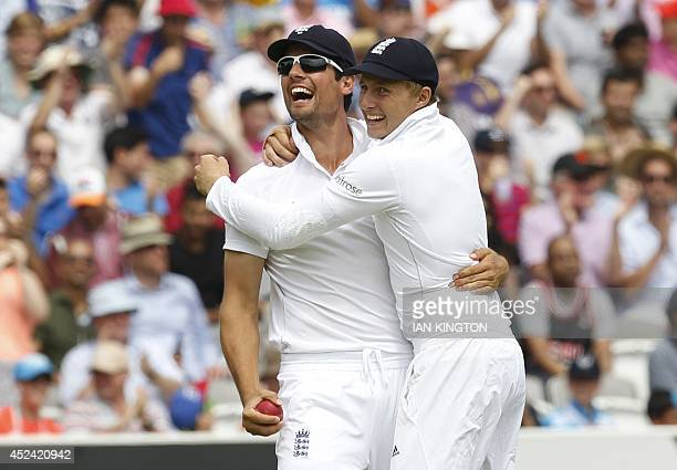 Englands Captain Alastair Cook celebrates with teammate Joe Root after taking the catch to dismiss Indias Stuart Binny for no runs during the fourth...