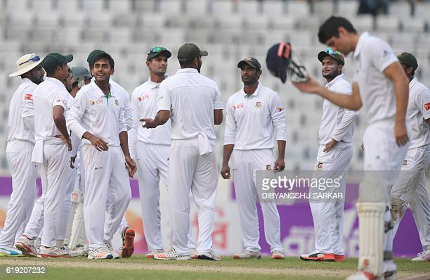 England's captain Alastair Cook looks on as Bangladesh Mehedi Hasan with teammates celebrates the wicket of Gary Ballance during the third day of the...