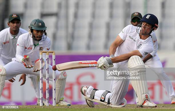 England's captain Alastair Cook plays a shot as Bangladesh' wicketkeeper Mushfiqur Rahim looks on during the third day of the second Test match...