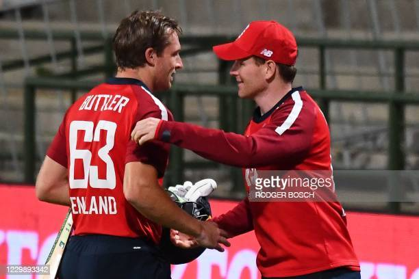 England's captain Eoin Morgan congratulates teammate England's Jos Buttler after their victory over South Africa during the third T20 international...