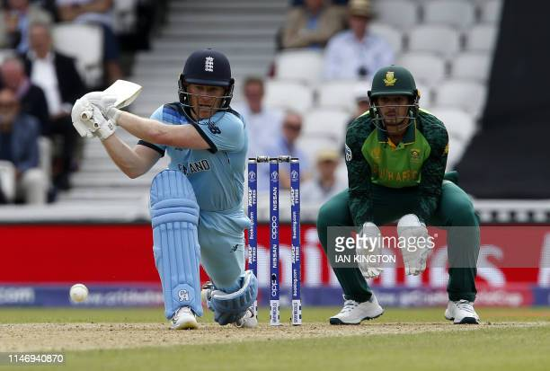 England's captain Eoin Morgan hits a reverse sweep watched by South Africa's Quinton de Kock during the 2019 Cricket World Cup group stage match...