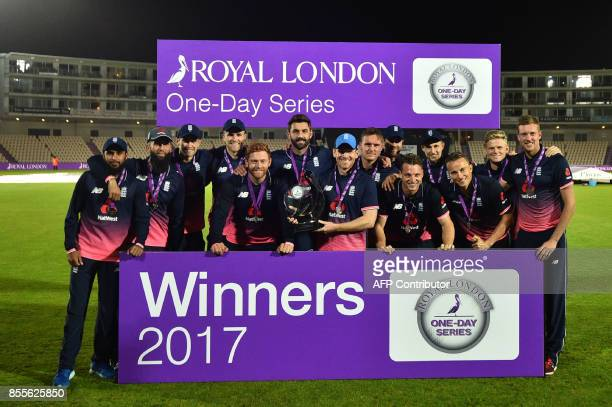 England's captain Eoin Morgan holds the trophy as England players celebrate victory of the OneDay International cricket series between England and...
