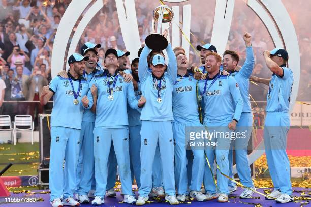 TOPSHOT England's captain Eoin Morgan lifts the World Cup trophy as England's players celebrate their win after the 2019 Cricket World Cup final...