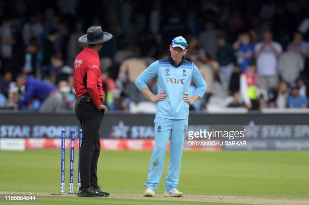 England's captain Eoin Morgan speaks with umpire Kumar Dharmasena as he looks at the wicket after the New Zealand innings during the 2019 Cricket...