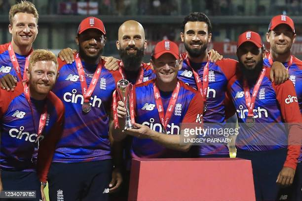 England's Captain Eoin Morgan , with teammates, raises the winner's trophy following the third T20 international cricket match between England and...