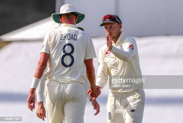 England's captain Joe Root congratulates teammate Stuart Broad on his bowling during the second day of the first cricket test between England and New...