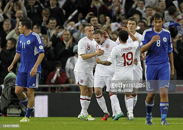 England's captain Wayne Rooney celebrates with teammates after scoring the opening goal from the penalty spot during the 2014 World Cup qualifying...