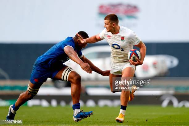 England's centre Henry Slade is tackled by France's flanker Cameron Woki during the final of the Autumn Nations Cup international rugby union series...