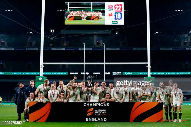 England's centre Owen Farrell holds up the trophy as England's players celebrate after their victory in the final of the Autumn Nations Cup...