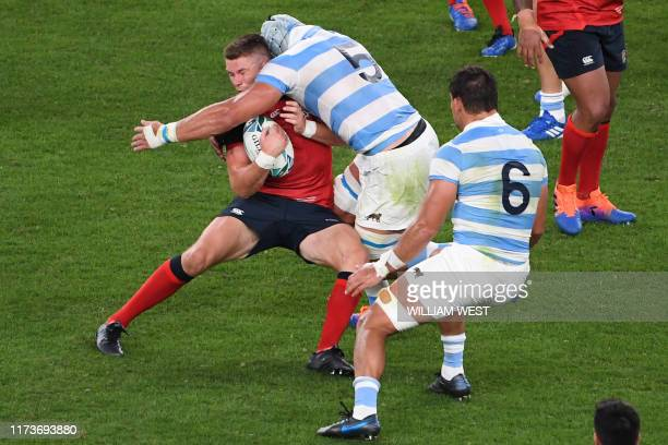 England's centre Owen Farrell is tackled by Argentina's flanker Pablo Matera during the Japan 2019 Rugby World Cup Pool C match between England and...