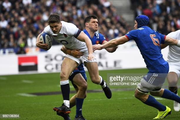 England's centre Owen Farrell is tackled France's winger Remy Grosso and France's flanker Wenceslas Lauret during the Six Nations international rugby...