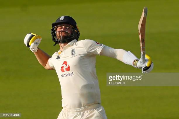 England's Chris Woakes celebrates after hitting the winning runs during play on the fourth day of the first Test cricket match between England and...