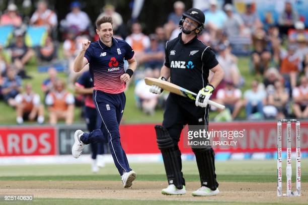 England's Chris Woakes celebrates the wicket of New Zealand's Colin Munro during the second oneday international cricket match between New Zealand...