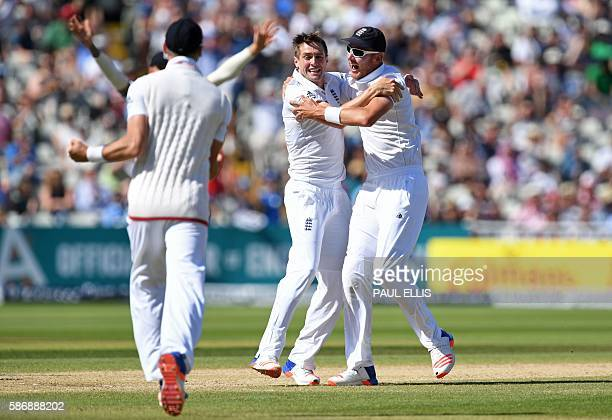 England's Chris Woakes celebrates with England's Stuart Broad after taking the wicket of Pakistan's Asad Shafiq during play on the final day of the...