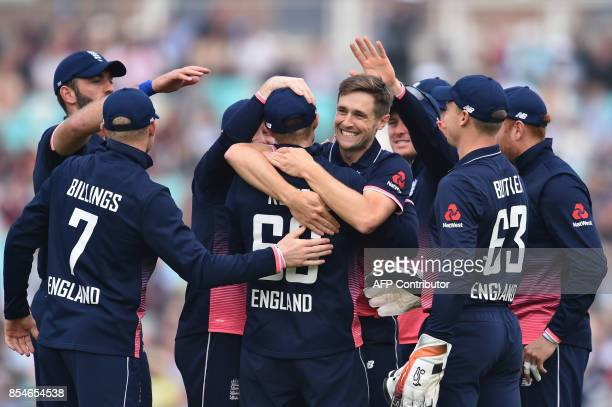 England's Chris Woakes celebrates with teammates the wicket of West Indies' Chris Gayle for two during the fourth OneDay International cricket match...