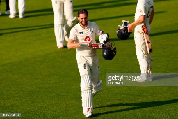 England's Chris Woakes smiles as he leaves the field having led England to victory on the fourth day of the first Test cricket match between England...