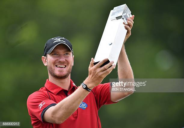 England's Chris Wood celebrates with the trophy after winning the golf PGA Championship at Wentworth Golf Club in Surrey south west of London on May...