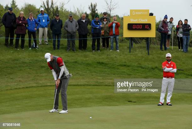 England's Chris Wood plays shot with the shot clock in the background as Andy Sullivan watches on during day one of the Golf Sixes at the Centurion...