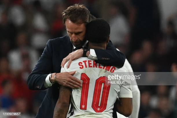 England's coach Gareth Southgate embraces England's forward Raheem Sterling after the UEFA EURO 2020 final football match between Italy and England...
