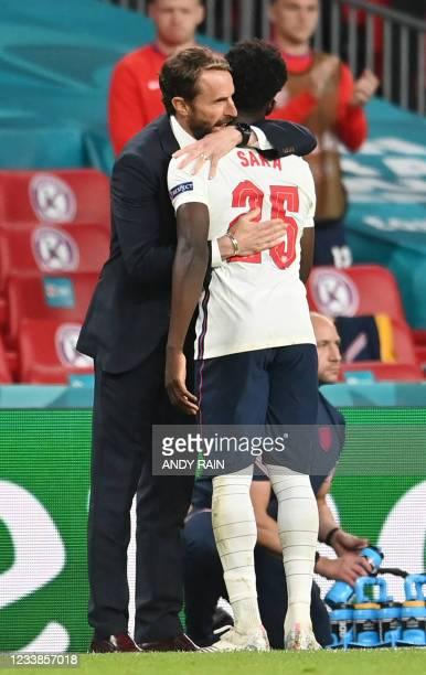 England's coach Gareth Southgate hugs England's midfielder Bukayo Saka as he leaves the pitch during the UEFA EURO 2020 semi-final football match...