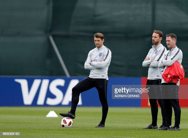 England's coach Gareth Southgate watches his team alongside Assistant Coaches Steve Holland and Allan Russell during a training session in Repino on...