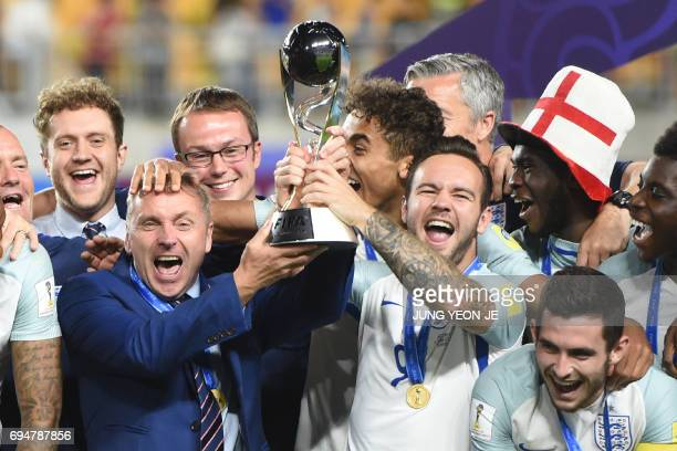 England's coach Paul Simpson celebrates with his players after winning the U20 World Cup final football match between England and Venezuela in Suwon...