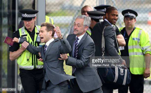 England's Comedian Lee Nelson is taken away by security at Luton Airport Luton