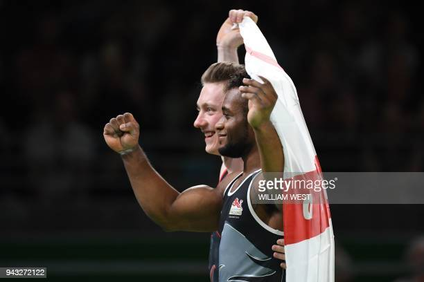 TOPSHOT England's Courtney Tulloch poses with teammate Nile Wilson after they came in first and second respectively in the men's rings final artistic...