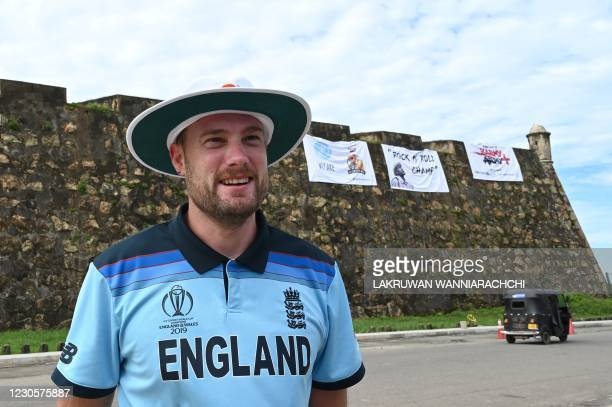 England's cricket fan Rob Lewis poses for photos at the ramparts of the Galle Fort overlooking the Galle International Cricket Stadium on the first...