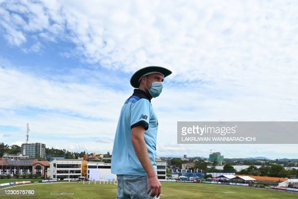 England's cricket fan Rob Lewis tries to watch the play from the ramparts of the Galle Fort overlooking the Galle International Cricket Stadium on...