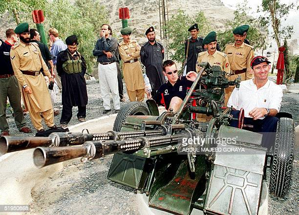 England's cricket players Ashley Giles and Andrew Caddick sit on an antiaircraft cannon during the English's team trip to the Khyber Pass an...