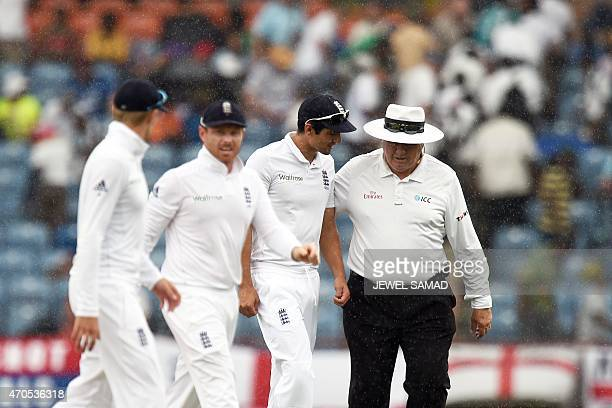 England's cricket team captain Alastair Cook along with other players and umpire leave field as rain pours during the second Test match between West...