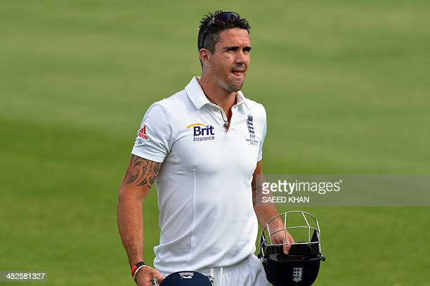 England's cricketer Kevin Pietersen walks back from the ground with a faulty helmet of a teammate Joe Root during day two play of the tour cricket...